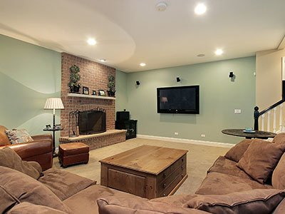 Basement family room with greenish walls, brick decor on the main wall, brown couch, wooden table, beige carpet, fireplace, and flat screen TV.