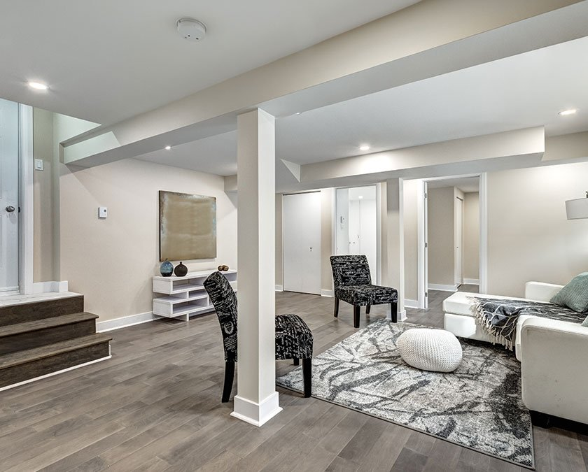 Basement family room with wooden floor, light beige painted walls, two gray chairs, white and black carpet, and white couch.