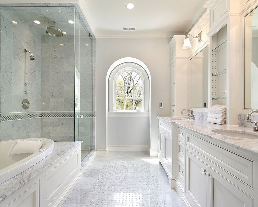 Modern bathroom with white marble floor, white cabinets, quartz countertops, large mirrors, and shower with glass doors.