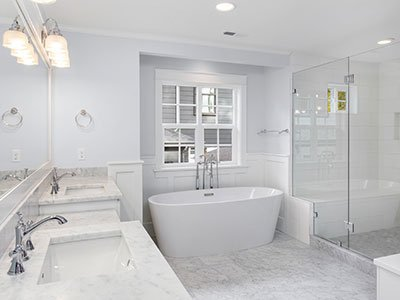 Modern bathroom with marble floor, white countertop, white cabinets, white tub, and shower with glass doors.